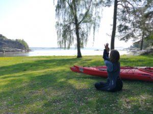 Kvinne i sittende yogastilling på gresset på en strand - fra pust og padleeventyr