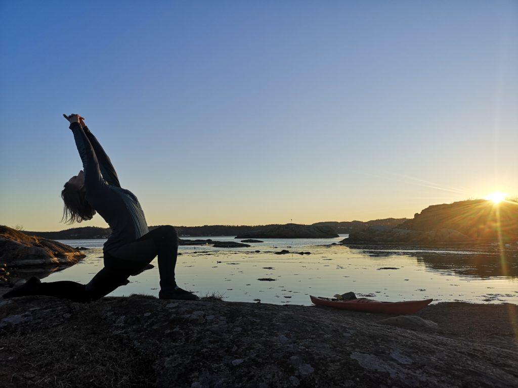 Kvinne i solnedgan i ståend yogastilling på svaberg